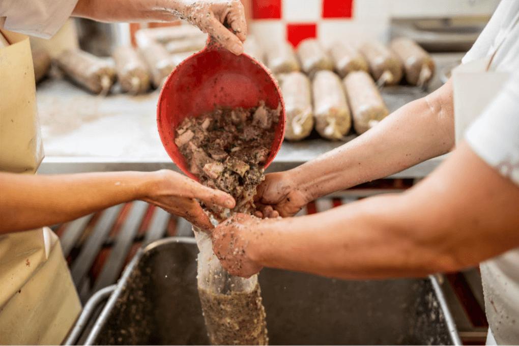 Dva zaměstnanci přesýpají kusy masa
