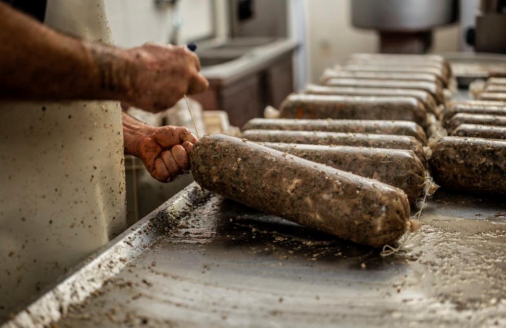 Pracovník váže velké hnědé klobásy do nožiček