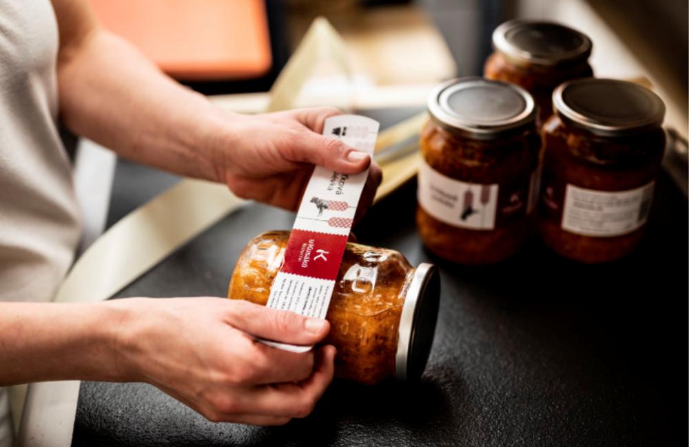 Pracovník nalepující etiketu na produkt v zavařeninové sklenici