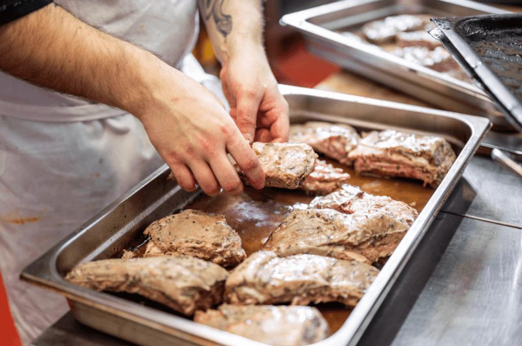 Kuchař připravující kusy masa