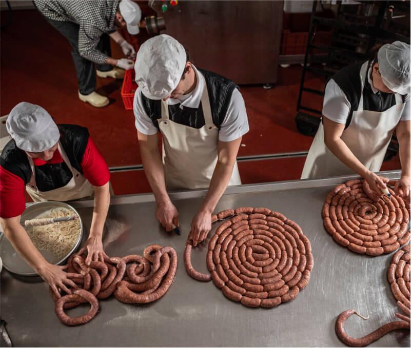 Pracovnící v zástěrách vyrábějící špekáčky