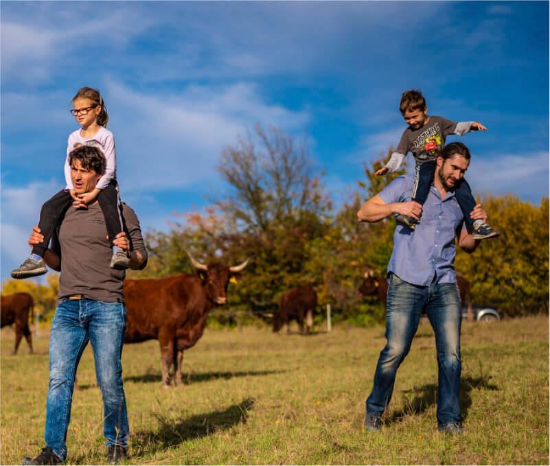 Majitelé řeznictví na pastvině mezi krávami nesoucí na ramenou svoje děti
